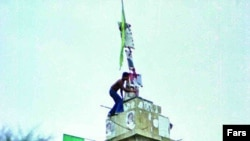 Iran -- A young boy on a tower installing a green flag and Khomeini's portrait, 1979