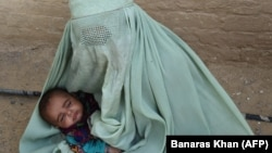 An Afghan refugee woman holds her baby at a United Nations repatriation center on the outskirts of Quetta, Pakistan.
