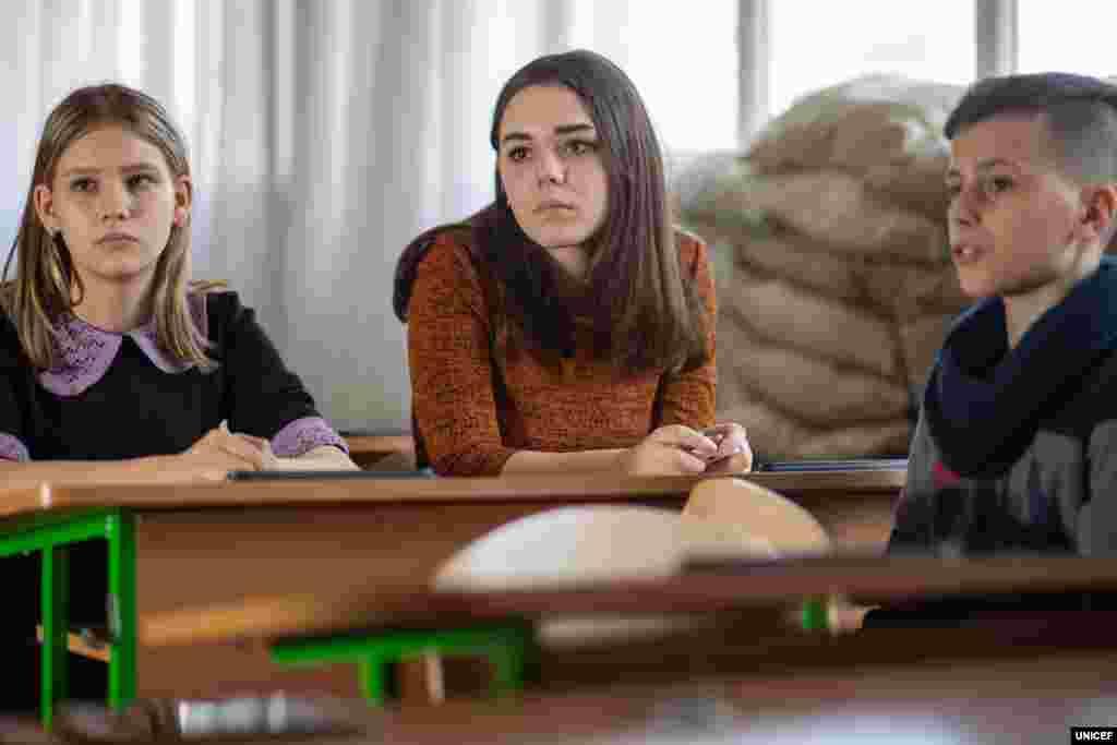 Зруйновані класи, вікна, закладені мішками з піском, щоб захищати дітей від випадкових куль – не найкраще місце для навчання. Проте більшість шкіл вздовж лінії розмежування на Донбасі мають такі інтер'єри. Марії (у центрі фото) 13 років, вона також навчається у Мар'їнській школі. Дівчина розповідає, що у 2014 році їй ледве вдалося врятуватися від обстрілу. Її матері наснився поганий сон, і вона вирішила, що в ту ніч потрібно заночувати в бабусі. «Того ж дня в наш будинок влучив снаряд. Ми там більше не живемо», – пригадує школярка.