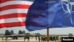 The U.S. and NATO flags fly in front of two U.S. Air Force F-22 Raptor fighter jets at the Lithuanian air base in Siauliai in April in a show of support for a region worried by Russian aggression in Ukraine.