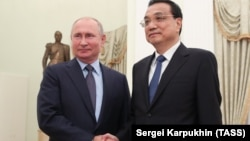 Russian President Vladimir Putin (left) meets with Chinese Premier Li Keqiang in Moscow on September 18.