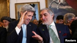 U.S. Secretary of State John Kerry speaks with Afghanistan's Chief Executive Abdullah Abdullah (R) during the Conference on Afghanistan in London on December 4.