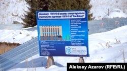 Көкжайлаудың батыс тарапында тұрған, құрылыс нысандарының сипаттамасы басылған баннер. Алматы, 1 желтоқсан 2014 жыл.