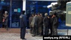 Задержанные мигранты стоят у здания суда. Алматы, 27 января 2011 года.