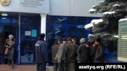 Задержанные полицией мигранты стоят у здания административного суда Алматы.