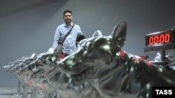 """Индийский художник Т.В.Сантош у своей работы Houndingdown (2007) на выставке """"Переписывая миры""""."""