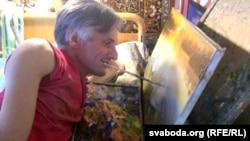 Анатоль Галушка малюе, трымаючы пэндзаль зубамі