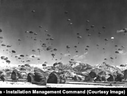 UN troops and equipment float to Earth during a massive airdrop in 1951.