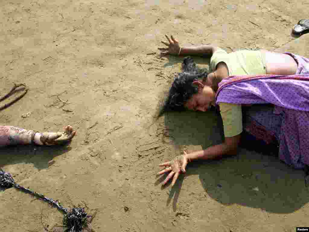 An Indian woman mourns the death of her relative (R) who was killed in tsunami on Sunday in Cuddalore, some 180 km (112 miles) south of the southern Indian city of Madras December 28, 2004. REUTERS/Arko Datta