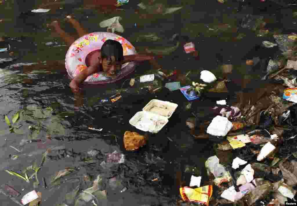 A child swims in the litter-strewn waters of Cilincing Beach in Jakarta, Indonesia.