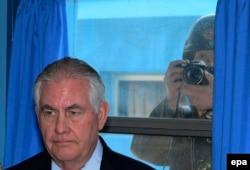 Военнослужащий Северной Кореи фотографирует государственного секретаря США Рекса Тиллерсона из окна во время его визита в пограничную «мирную» деревню Пханмунджом на межкорейской границе. 17 марта 2017 года.