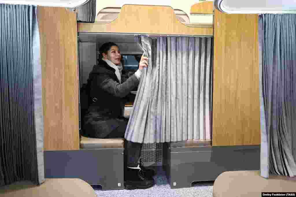 Женщина открывает шторки в выставленном в Сочи макете вагона. Александр Лошманов, представитель подразделения «Трансмашхолдинг» компании РЖД, которое будет производить новые вагоны, говорит, что пассажиры смогут самостоятельно и индивидуально настроить вентиляцию.
