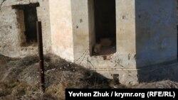 Проволока ограды прикреплена к вбитому в древнюю стену гвоздю