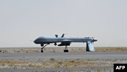 A U.S. Predator unmanned drone armed with a missile sits on the tarmac of Kandahar military airport.
