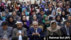 Afghan Chief Executive, Abdullah Abdullah (C) prays during an event marking International Women's Day, in Kabul on March 8