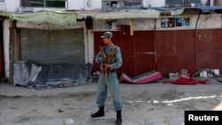 An Afghan policeman stands guard at the site of a deadly suicide attack in Kabul on September 29.