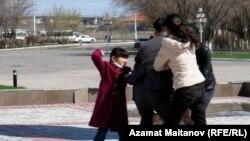 Полицейские, несмотря на попытки детей защитить мать, тащат участницу пикета Райхан Алиханову в полицейский участок. Атырау, 25 апреля 2011 года.