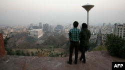 A couple stands at a viewpoint overlooking Tehran, which is covered in smog.