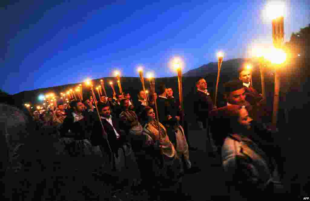 Men and women with torches participate in the wedding procession the night before a typical marriage in the western Macedonian village of Galicnik, some 150 km southwest of the capital, Skopje, on July 16. Every year, around the time of the Christian Orthodox St. Peter's Day holiday, Macedonians originating from Galicnik gather in this almost deserted mountainous village and a couple gets married according to the old traditions of this region.Photo by Robert Atanasovski for AFP