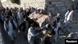 Relatives and residents carry a coffin for burial of one of the victims of a suicide attack in Asadabad, the capital of Kunar Province, on February 27.