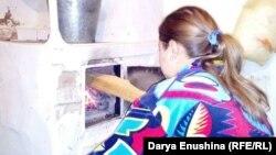 Светлана Корелева топит печь