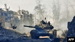 یکی از تانکهای ارتش سوریه در حال عبور از ویرانههای منطقه قصر العدلی که به تازگی از شورشیان بازپس گرفته شده است