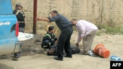 Rescuers help a victim following a mortar attack on the western city of Ramadi, the provincial capital of Anbar province on April 15.