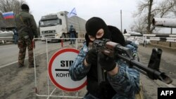 "Armed masked men who describe themselves as members of Ukraine's disbanded elite ""Berkut"" police force at a checkpoint under Russian national and Russian naval flags on a Crimean highway."