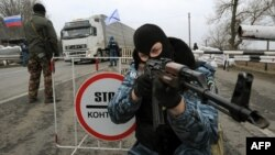One of the armed masked men who call themselves members of Ukraine's disbanded elite Berkut riot-police force aims his rifle at a checkpoint on a highway that connects Crimea to mainland Ukraine near the city of Armyansk on February 28