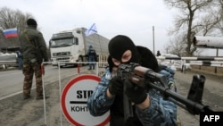"""Вооруженный мужчина в одежде расформированного милицейского подразделения """"Беркут"""" на блок-посту в Армянске. 28 февраля 2014 года."""
