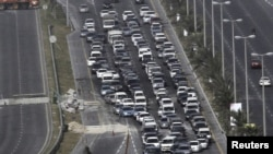 Cars line up at a checkpoint set up by Gulf Cooperation Council forces deployed in Bahrain.