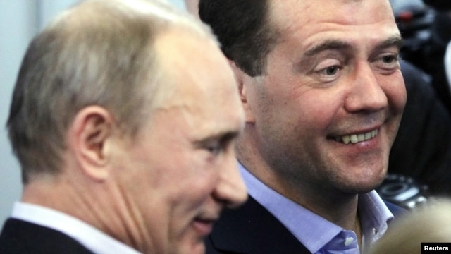 Prime Minister Vladimir Putin (left) and President Dmitry Medvedev try to smile as they visit the headquarters of the United Russia party after voting closed in Moscow on December 4.