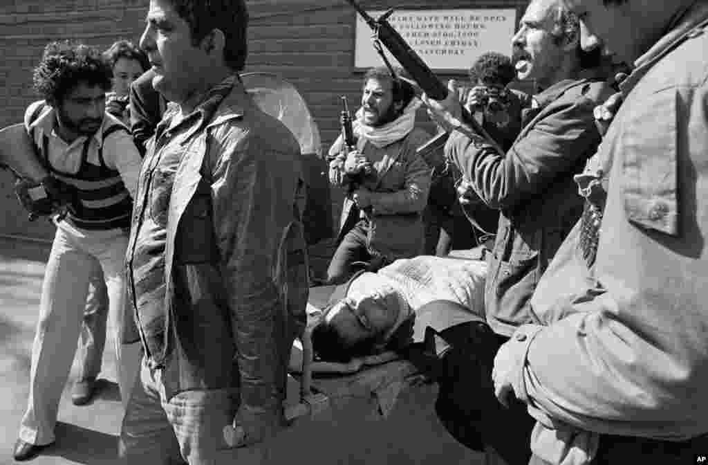 A shooting victim is carried away from the U.S. Embassy by armed men loyal to Ayatollah Khomeini after they had stormed the compound.