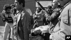 აიათოლას ერთგულ მომხრეები. აშშ-ის საელჩოდან სროლისას დაჭრილი ადამიანი საკაცით გამოჰყავთ.