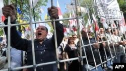 """Сторонники экс-премьера Юлии Тимошенко требуют, чтобы президент Виктор Янукович """"ответил, за что он пытает и убивает Тимошенко"""". Киев, 27 апреля 2012 года"""