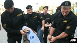 Riot police detain an opposition supporter in Minsk during a protest against Belarus and Russia military exercises in September 2009.