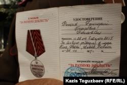 """Удостоверение к медали """"За ратную доблесть"""", которой Григорий Рощин, по его словам, награжден за """"разведку"""" в Украине. Фотография удостоверения сделана в Алматы 17 сентября 2014 года."""