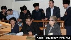 Активистов Серикжана Мамбеталина и Ермека Нарымбаева ввели в пятницу в зал суда в наручниках, пристегнутых с двух сторон к полицейским. Алматы, 8 января 2016 года.