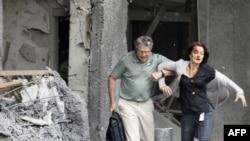 Одной из пострадавших помогают выбраться из поврежденного при взрыве здания