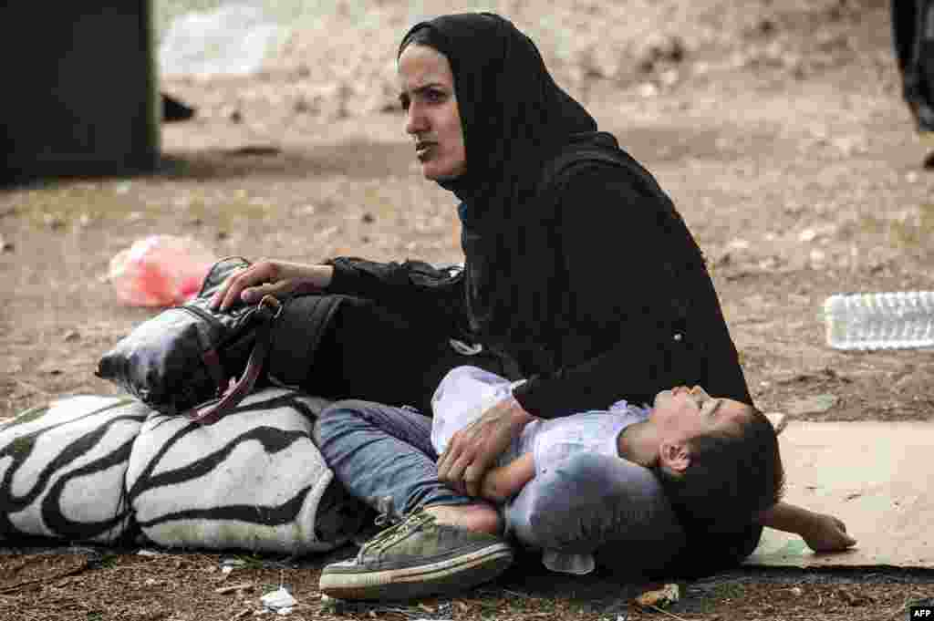 A child rests on the knees of a woman in a refugee center in Presevo, Serbia. (AFP/Armend Nimani)