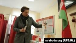 Женщина бросает бюллетень в урну для голосования. Минск, 11 октября 2015 года.