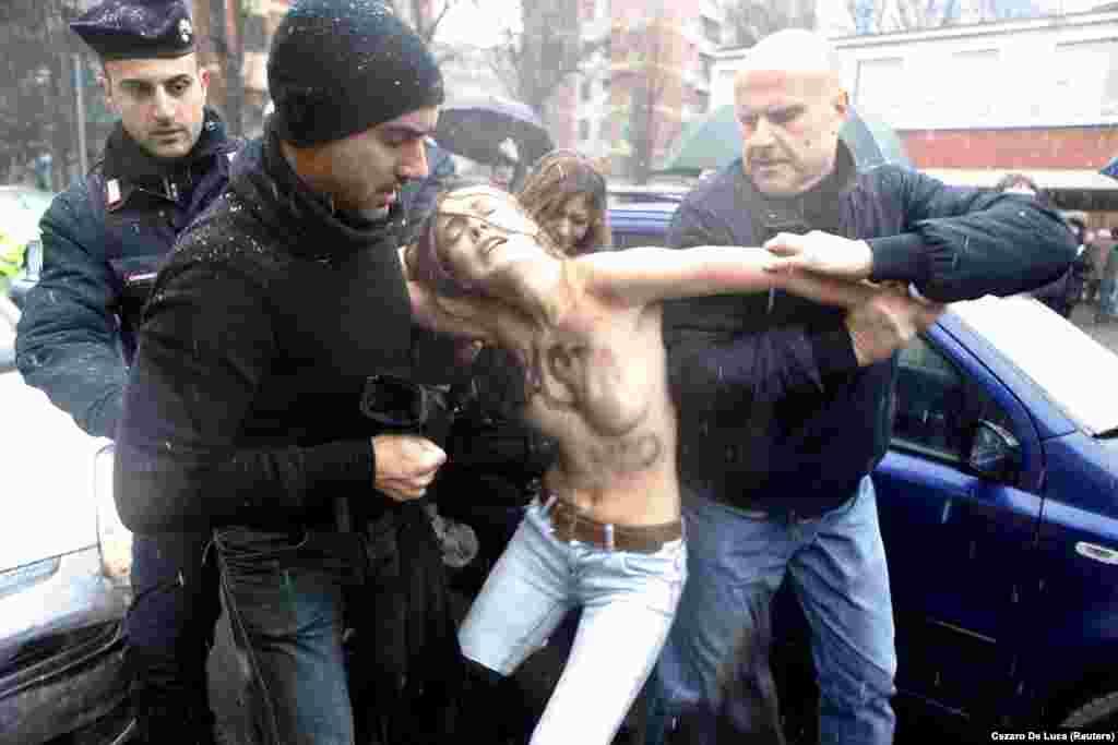 Поліція виводить Шачко з виборчої дільниці в Мілані, де голосував колишній прем'єр-міністр Італії Сільвіо Берлусконі. 2013 рік