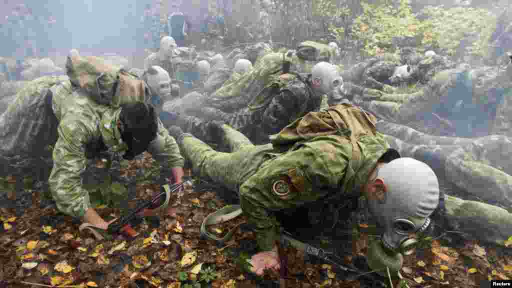 Servicemen from a Belarusian Interior Ministry special unit wear gas masks and crawl on the ground during a test near the village of Horany. (Reuters/Vasily Fedosenko)