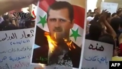 A screen grab from footage uploaded to YouTube that shows a protester burning a picture of Syrian President Bashar al-Assad during an anti-regime student demonstration in Damascus, reportedly on September 19.