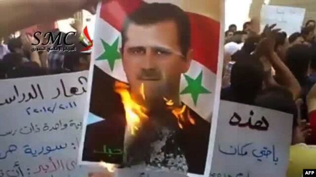An image grab from footage uploaded on YouTube shows a protester burning a picture of Syrian President Bashar al-Assad during an antiregime demonstration in Damascus in September.