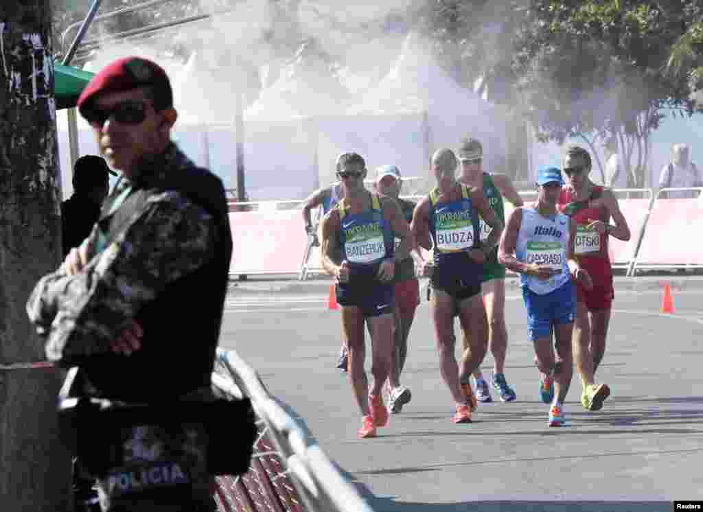 Competitors get some welcome relief from the searing heat while passing through a mist station in the men's 50-kilometer walk.