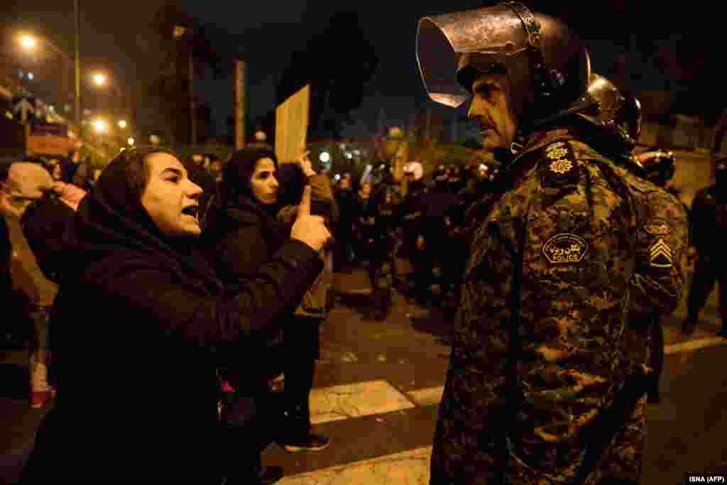 A woman attending a candlelight vigil for the victims of the Ukrainian airliner crash talks to a policeman on January 11 at Tehran's Amir Kabir University.