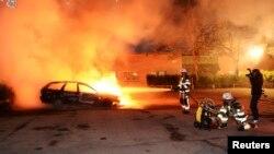 Пожежники гасять палаючий автомобіль в Стокгольмі, 21 травня 2013 року