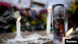 Candles burn alongside a photograph of Nelson Mandela outside the Medi-Clinic Heart Hospital in Pretoria, where the ailing former president is being treated.