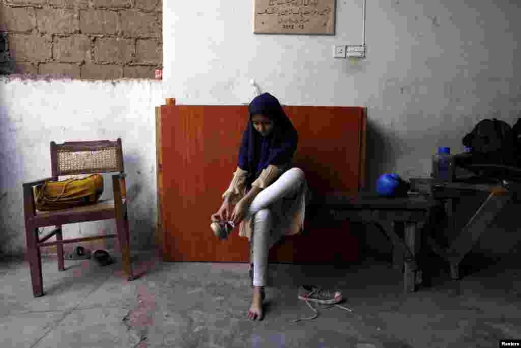 Tabia, 12, removes her shoes after finishing a training session.
